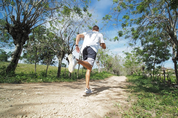 스포츠 흰색 옷을 입은 남자 주자는 자연의 흔적을 따라 실행됩니다. 다시보기.