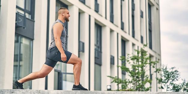 Бегун человек разминает ноги делает растяжку перед тренировкой, стоя на лестнице на улице