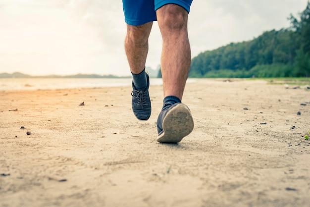 Man runner legs running closeup on shoe, men jogging on the beach