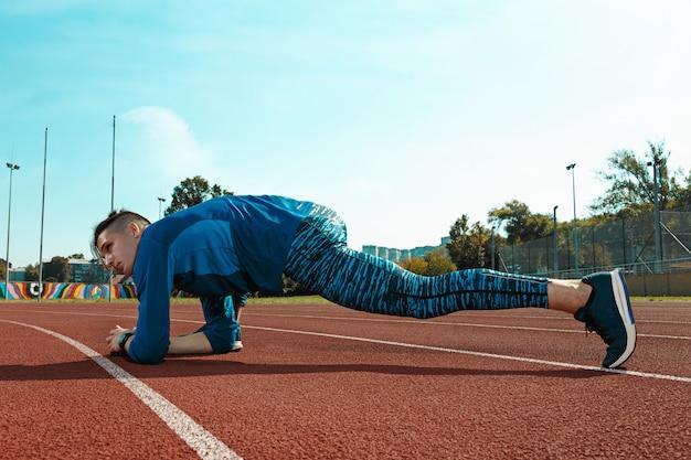 ウォーミングアップを行うスタジアムトラックで実行トレーニングの準備をして足を伸ばし男ランナー