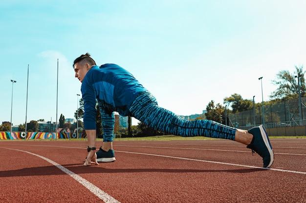 ウォーミングアップを行うスタジアムトラックでのランニングトレーニングの準備をして足を伸ばして男ランナー