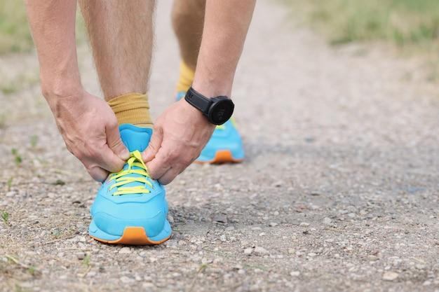 맨 러너는 손 스포츠와 조깅 컨셉으로 바닥에 신발끈을 묶는다