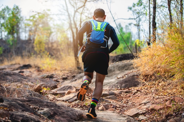 A man runner of trail . and athlete's feet wearing sports shoes for trail running in the forest