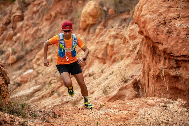 A man runner of trail . and athlete's feet wearing sports shoes for trail running in the mountains