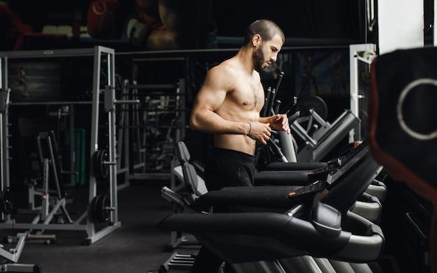 Человек работает в тренажерном зале на беговой дорожке концепции для занятий спортом, фитнеса и здорового образа жизни. фото высокого качества