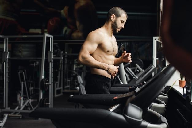 フィットネスと健康的なライフスタイルを行使するためのトレッドミルのコンセプトでジムで走っている男