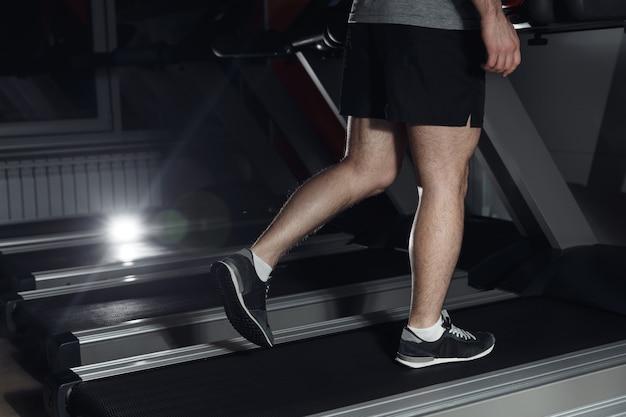 運動、フィットネス、健康的なライフスタイルのためのトレッドミルのコンセプトでジムで走っている男。