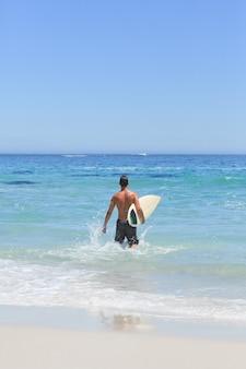 彼のサーフボードでビーチで走っている男