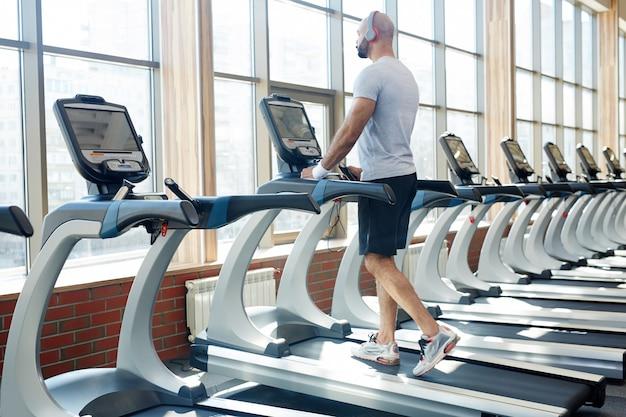 Человек работает на беговой дорожке в современном тренажерном зале