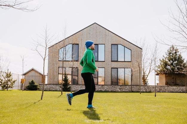 裏庭の田園地帯で朝屋外で走っている男健康的なアクティブな男ジョギング