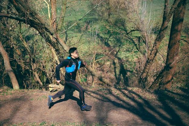 Uomo che corre in un parco o in una foresta contro lo spazio degli alberi