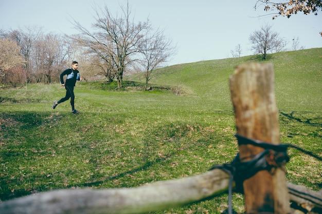 Uomo che corre in un parco o in una foresta contro gli alberi