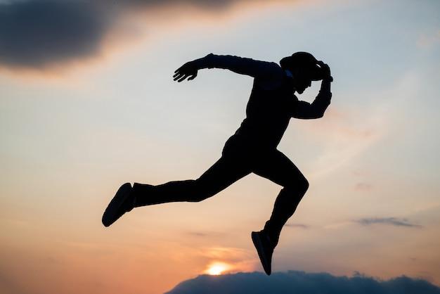 일몰 하늘, 지구력에 대한 에너지로 가득 찬 체력으로 실루엣을 달리는 남자.