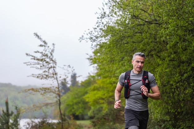 Человек бежит через туманный зеленый куст рядом с озером