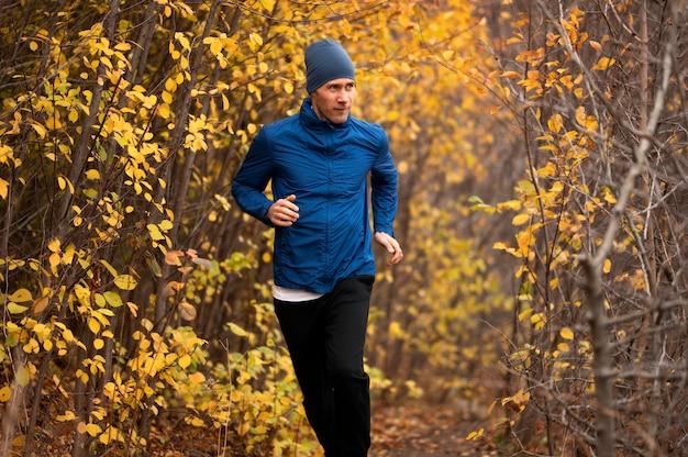 Uomo che corre sul sentiero nella foresta
