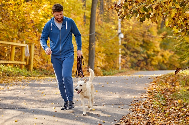 Man running with pet dog in the autumn forest, guy enjoy jogging with white purebred dog in the nature