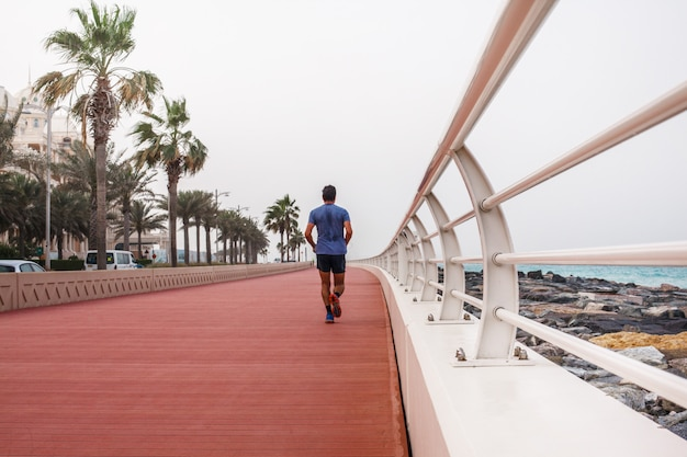 A man runs along a beautiful promenade with a white fence.