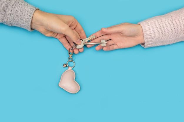 青の家からの心で新しいキーを保持している男性と女性の手。