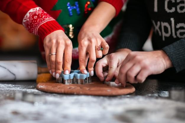 テーブルでクッキーを作る赤と灰色の冬のセーターで男性と女性の手。