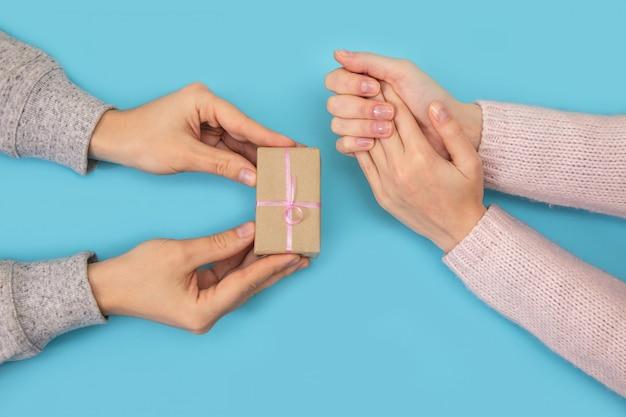 男と女の手が青のギフトボックスを保ちます。