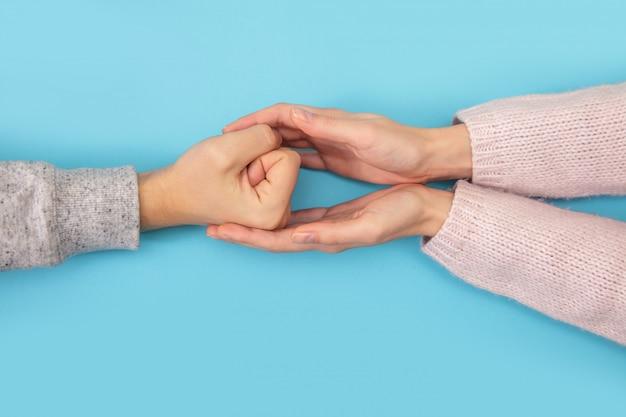 男性の手と女性の手がお互いを青に保ちます。
