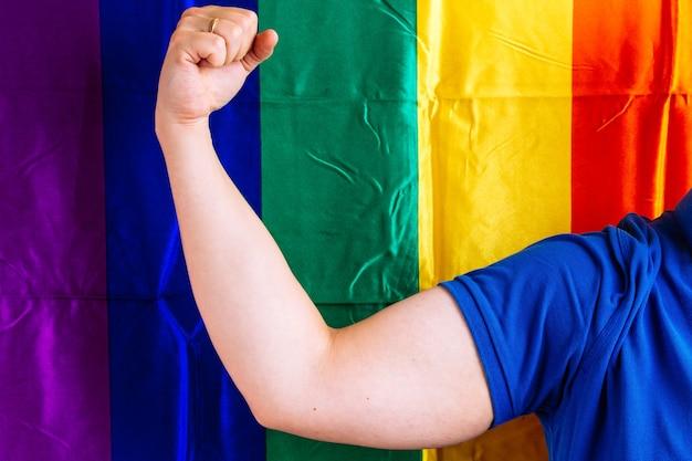 背景にlgbtqフラグと強さの概念の上腕二頭筋を示す結婚指輪と手を持つ男の腕。同性愛の結婚の概念