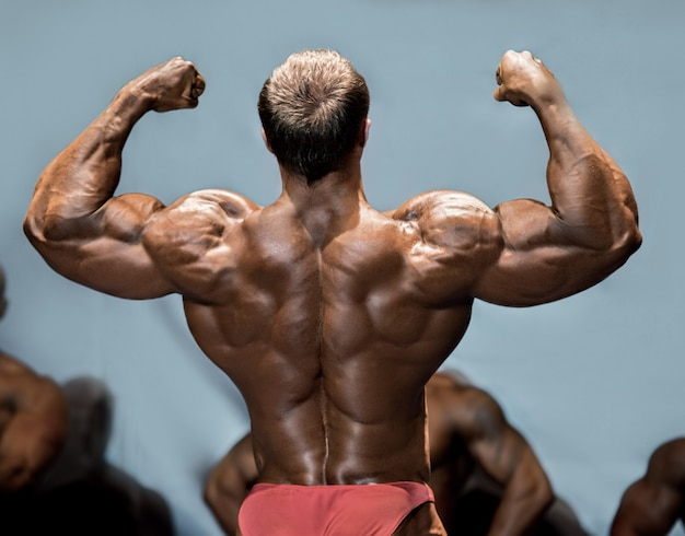 Man's back double biceps pose. bodybuilder demonstrating arms on stage. making opponents envious. one more step to victory.