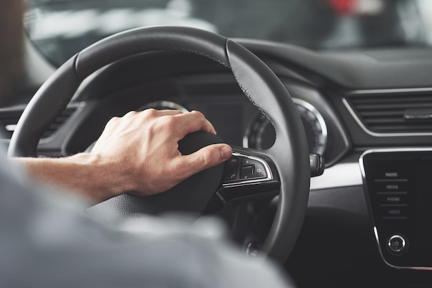 Man's big hands on a steering wheel while driving a car.