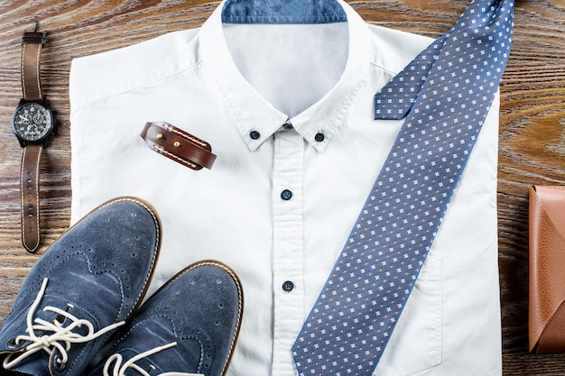 Man's classic clothes outfit flat lay with formal shirt, tie, shoes and accessories.