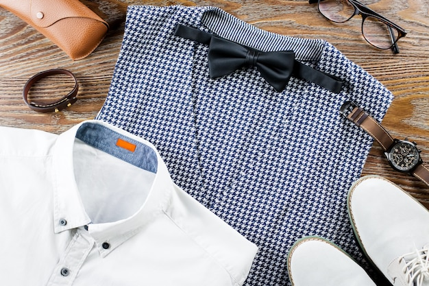 Man's classic clothes outfit flat lay with formal shirt, vest, bowtie, shoes and accessories