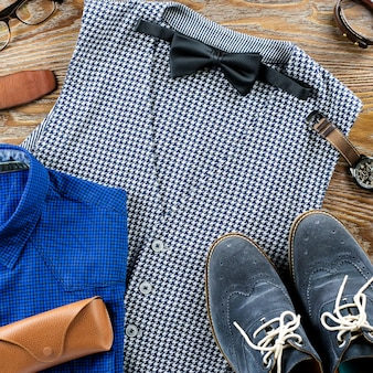 Man's classic clothes outfit flat lay with formal shirt, vest, bowtie, shoes and accessories.