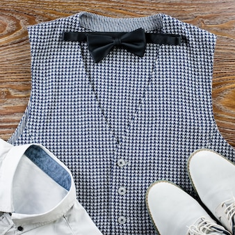Man's classic clothes outfit flat lay with formal shirt, vest, bowtie, shoes.