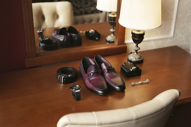 Man's classic shoes, belt, toilette, perfume, and wedding rings