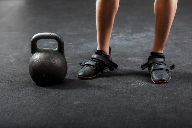 A man's feet in black sneakers with black gymnastic kettlebell