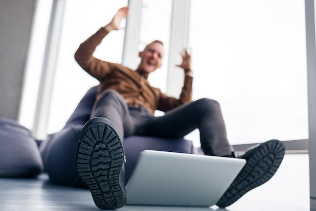 A man's foot in shoes is near the laptop. man wants to step on his laptop