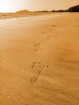 The man's footprints on the sand beach on vacation holiday relaxing time