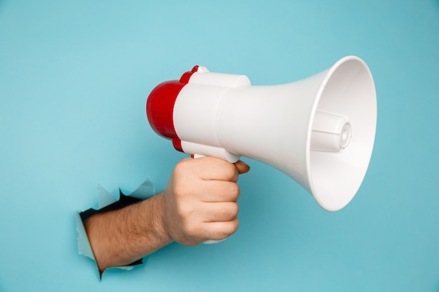 Man's hand arm hold megaphone isolated through torn blue background.