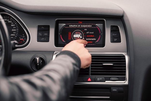 Мужская рука выбирает стиль вождения на бортовом компьютере автомобиля.