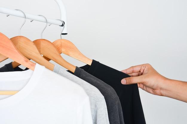 나무 옷걸이에 검은 색, 회색 및 흰색 티셔츠의 컬렉션에서 검은 색 티셔츠를 선택하는 사람의 손