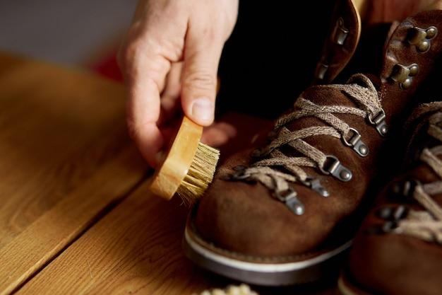 Мужская рука чистит замшевую обувь щеткой на деревянном полу