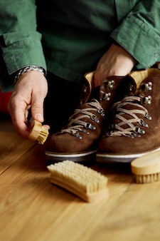 Man's hand cleaning suede shoes with a brush on wooden floor
