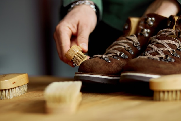 Man's hand cleans suede shoes with brush