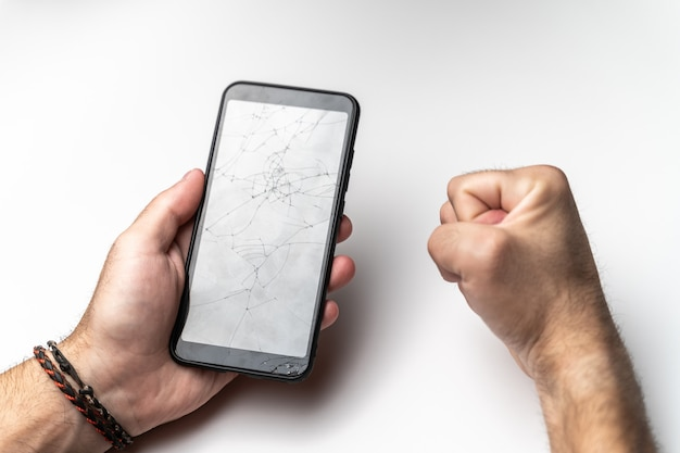 A man's hand and a clenched fist with a mobile phone with a broken screen.