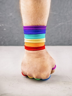 Man's hand clenched into a fist with  rainbow-colored bracelet hits concrete wall, concept of protecting the rights of lgbt people, pride