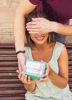 La mano dell'uomo che chiude gli occhi della sua ragazza dando un regalo a sorpresa