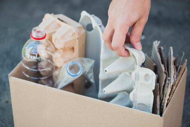 Man's hand collecting plastic bottles and egg carton in the recycle box