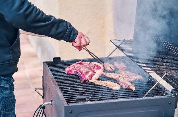 바베큐 그릴에 큰 쇠고기 스테이크를 요리하는 남자의 손.