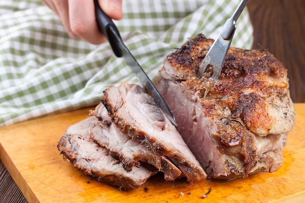 Man's hand cuts the baked meat with a knife on cutting board