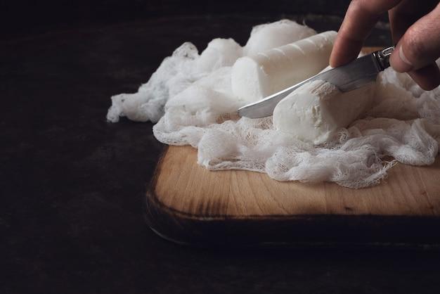 人間の手で切る、スライスする、ナイフでフレンチゴートチーズ、軟質チーズ、伝統的な前菜、スナック、素朴な金属の背景にデザート