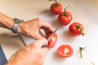 Man's hand cutting tomato on chopping board